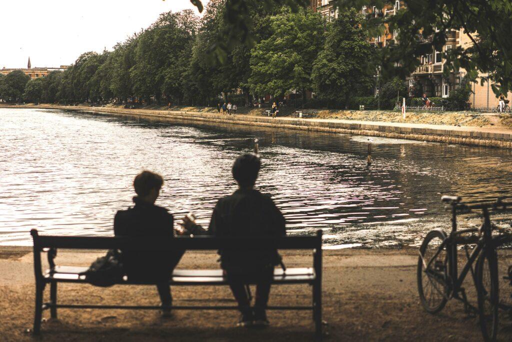 Par sidder på bænk ved søerne på Nørrebro